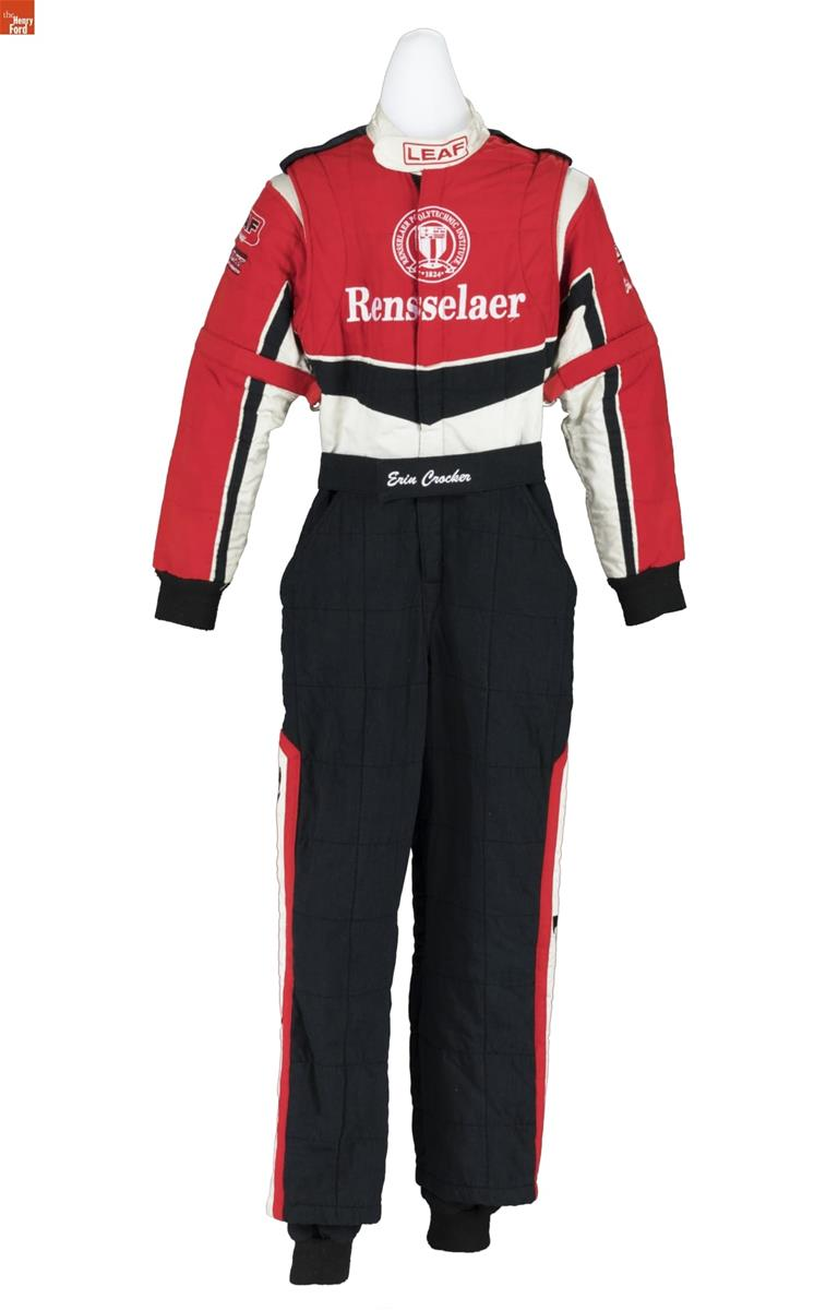 Jumpsuit with black pants with red trim on sides and red, black, and white bodice and sleeves containing text
