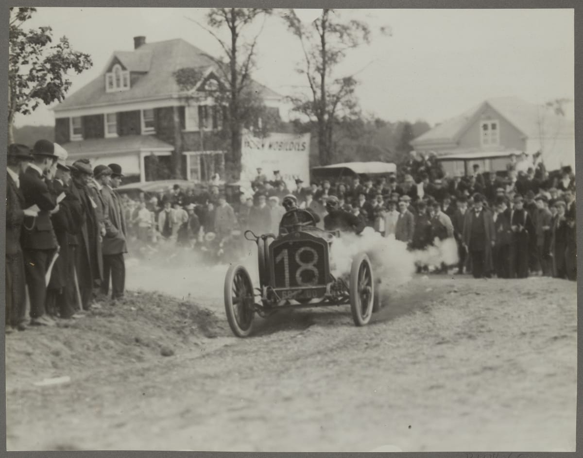 Early open race car careens around a corner on a dirt road, kicking up clouds of smoke with spectators looking on and houses in the background