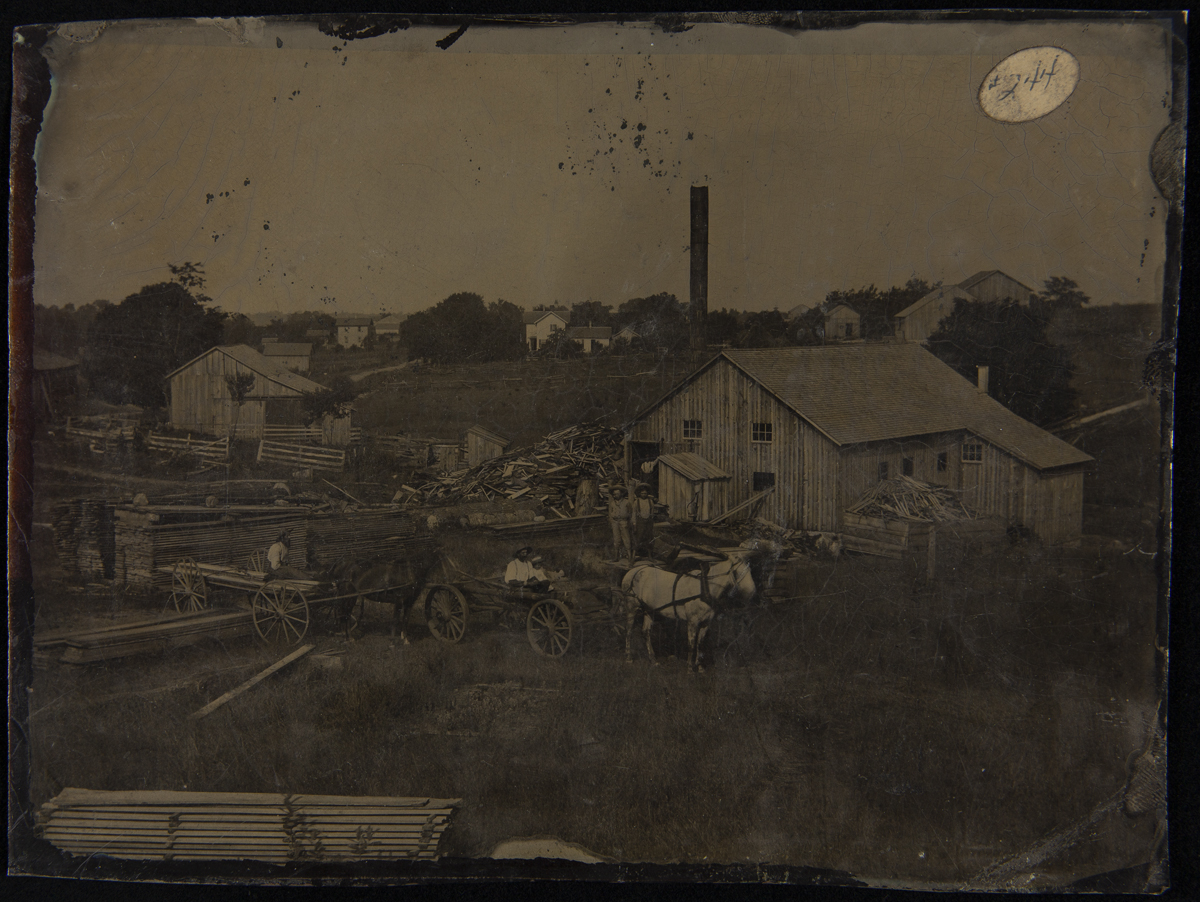Landscape with wooden buildings, stacks and piles of lumber, horses and wagons, and people