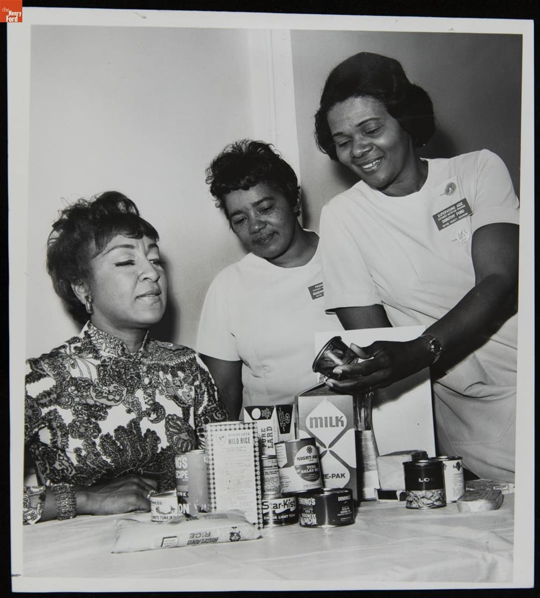 Three women of color standing and sitting around a table containing canned, boxed, and bagged food items