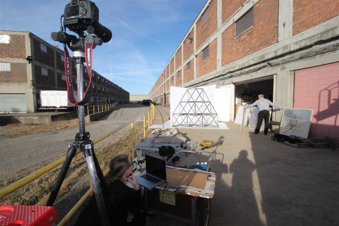 Camera on tripod in foreground pointing toward white paper with metal truss in front of it alongside a large red brick building