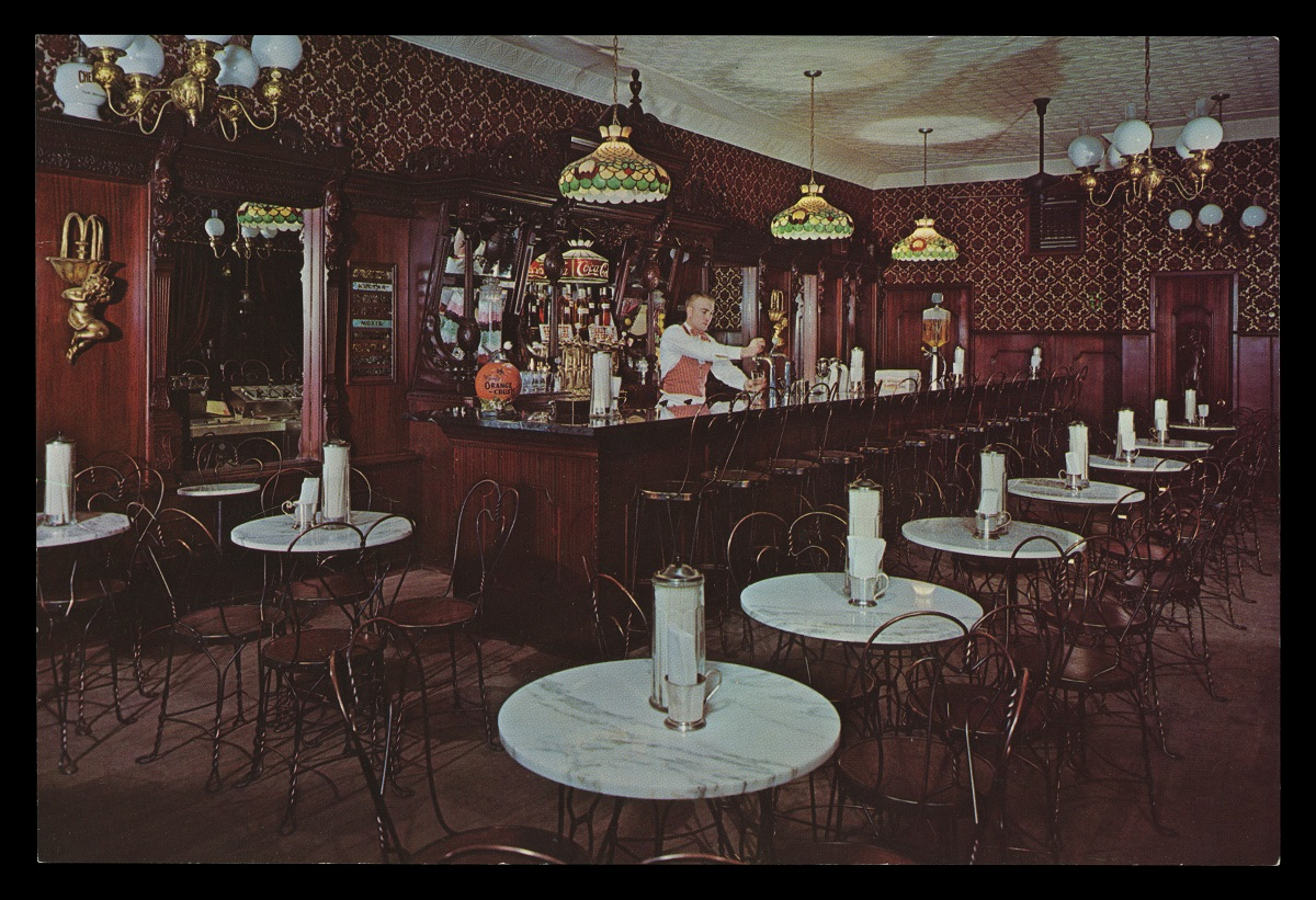 Elaborately decorated Victorian-style ice cream parlor with small marble tables and wire chairs
