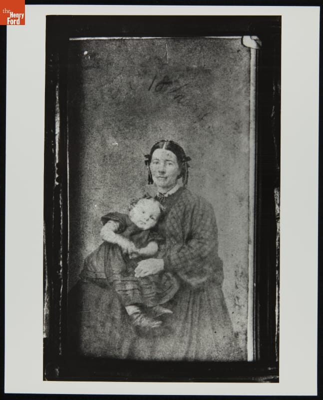 Framed portrait of woman in dress with hair in two long coils on either side of her face, holding a young child