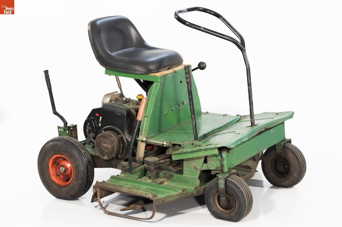 Minimal riding lawnmower, with open green base topped with black seat with machinery underneath
