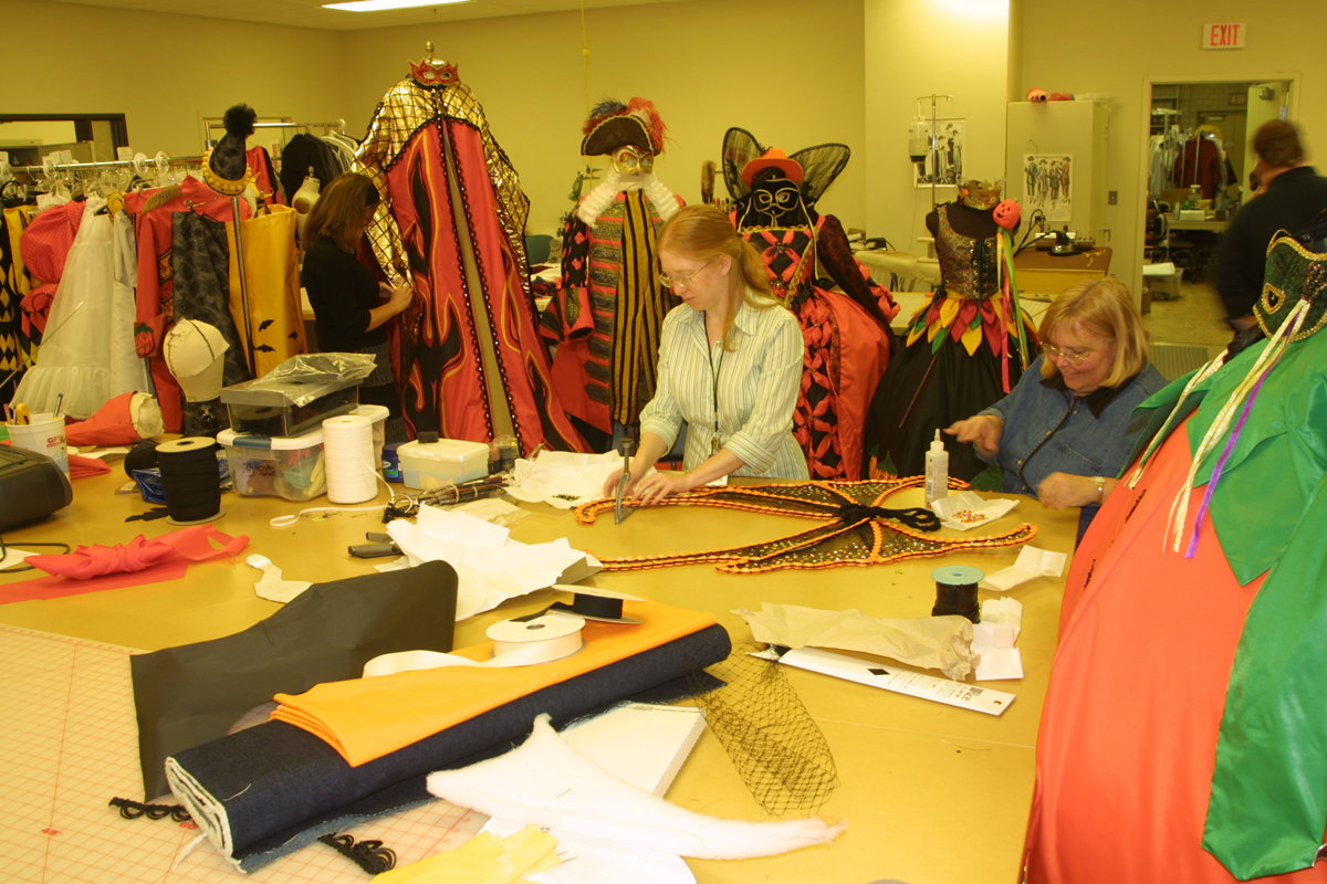 Two women work at a large table filled with fabric bolts and sewing notions; elaborate costumes hang in the background