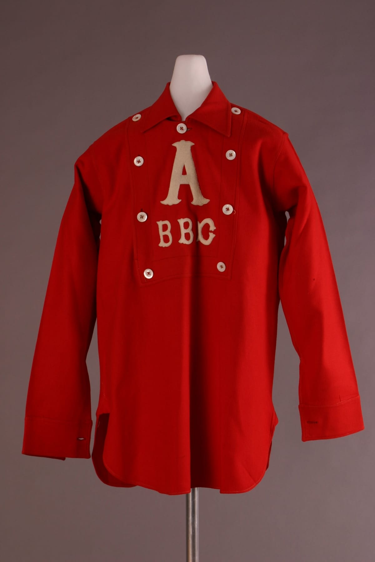 "Red shirt with collar and white buttons around the placket, featuring white letter ""A"" followed by ""BBC"""