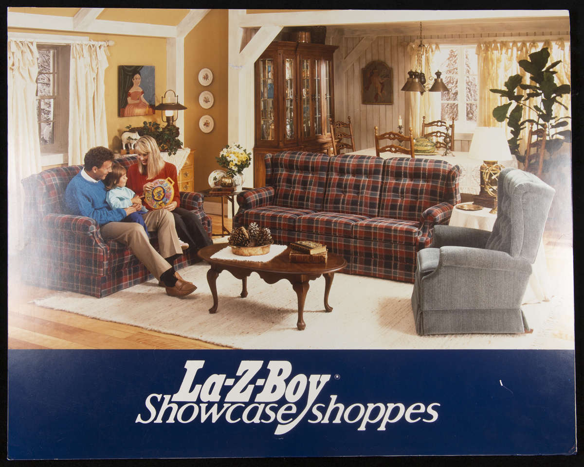"La-Z-Boy Showcase Shoppes, 1980-1988	Living room with woman, man, and child on couch, with text ""La-Z-Boy Showcase shoppes"" below"