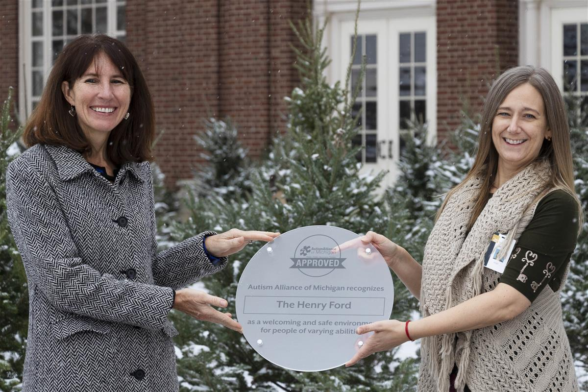 Two women hold a frosted plastic plaque with text in front of snow-covered evergreens and a brick building