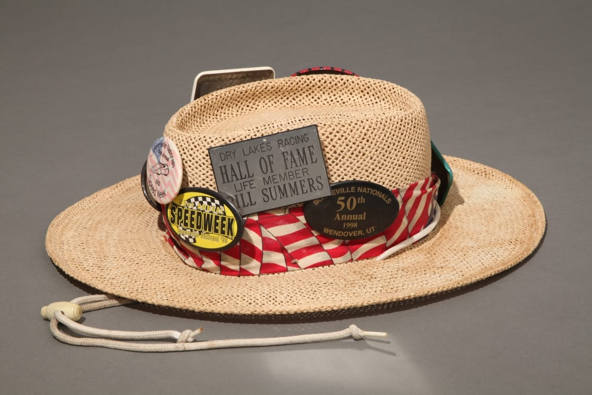 Straw hat with red and white striped band and many buttons and badges containing text and images