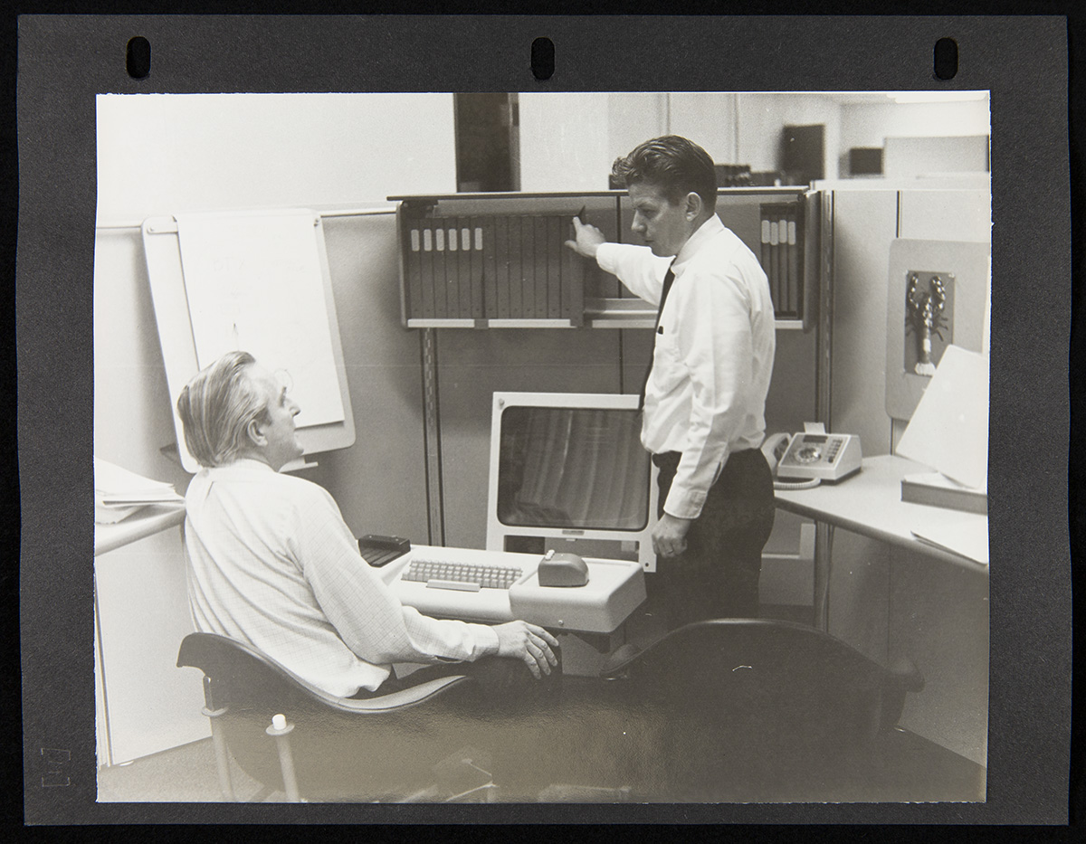 Two men, one seated and one standing, among office furniture holding a computer, phone, and books or binders