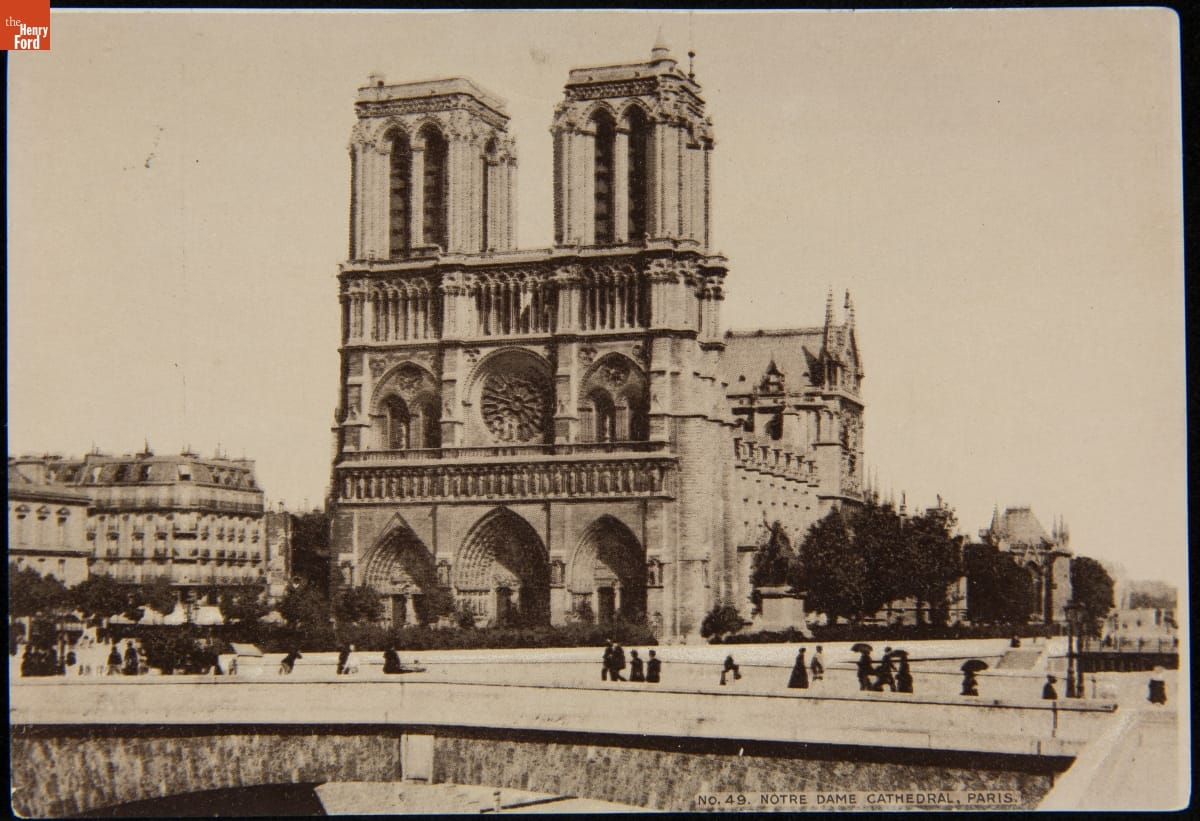 Black-and-white photo of gothic cathedral; people passing on roadway in front and other buildings visible to the side