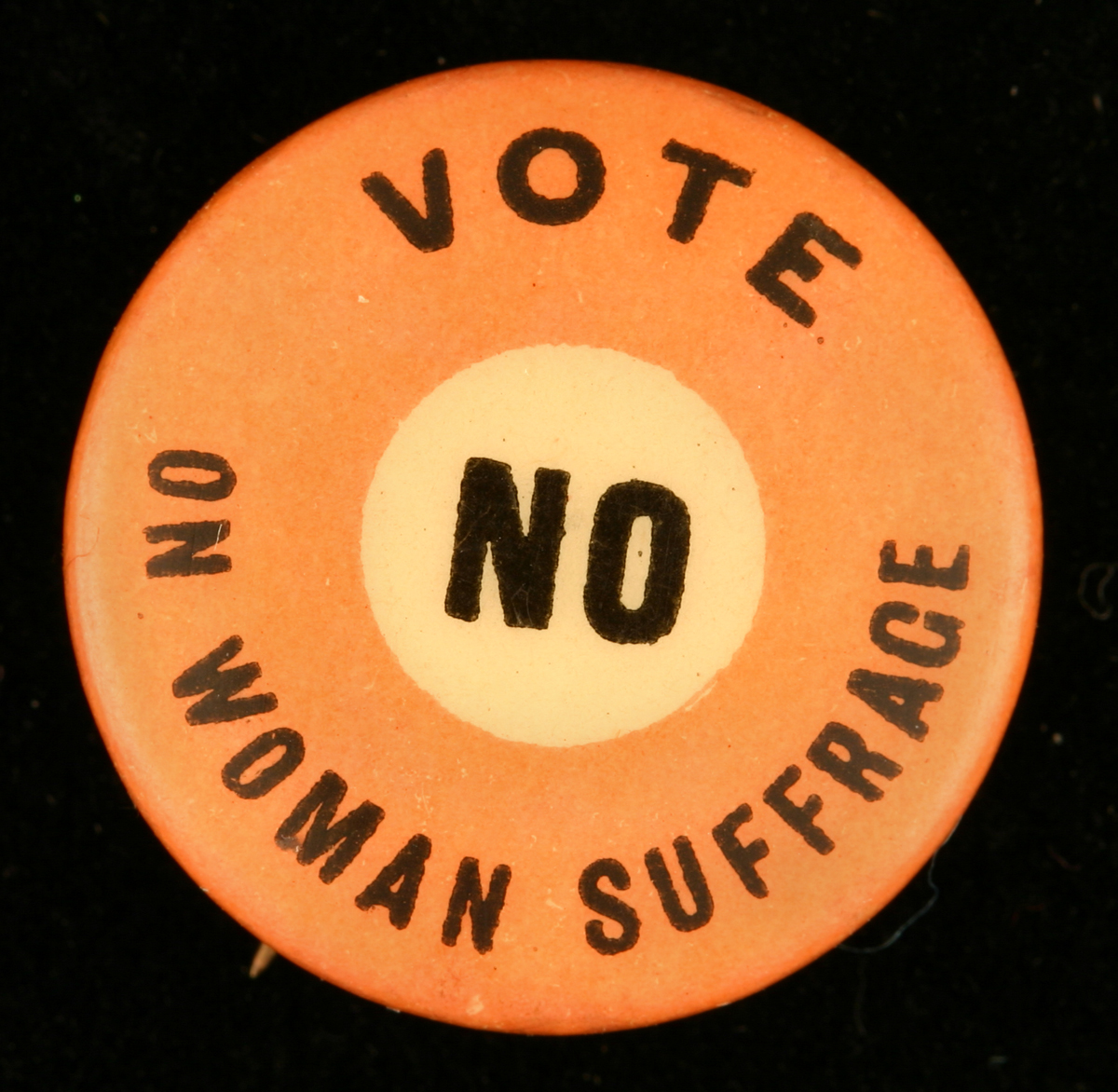 "Round orange button with yellow circle in center, with printed text reading ""Vote no on woman suffrage"""