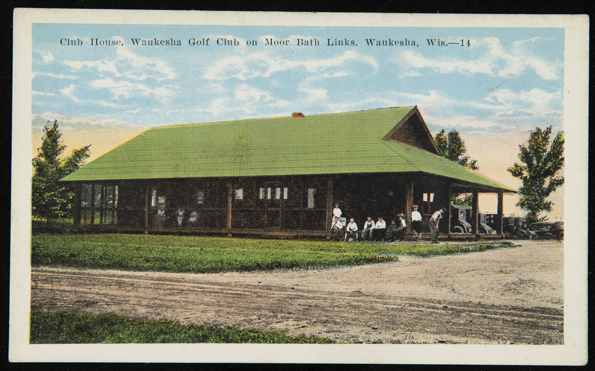 Postcard of open wooden building with green roof, with people sitting and standing on porch; also contains text