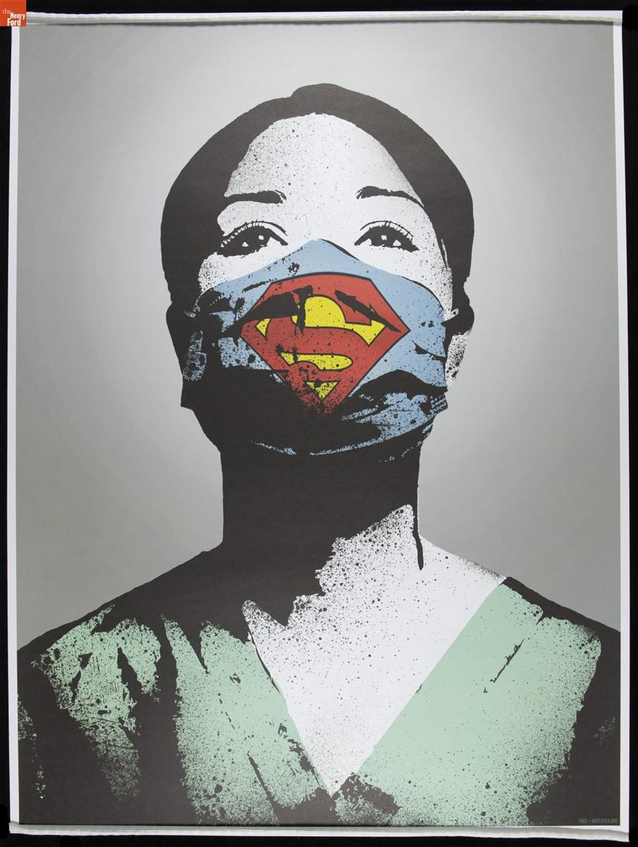 "Portrait of woman with dark hair in green scrubs wearing blue face mask marked with yellow and red ""Superman"" symbolic S"