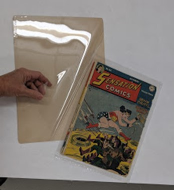 Hand sliding comic book onto a board with plastic over top