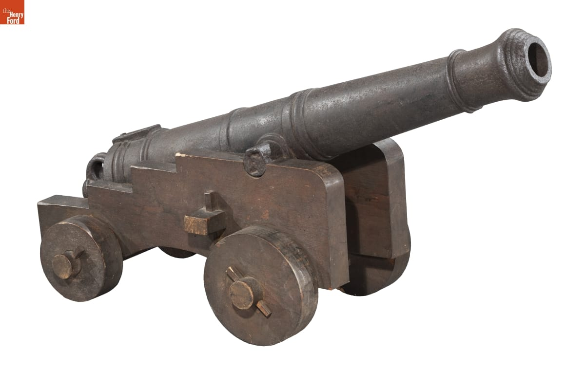 Metal cannon with some decorative banding, mounted on a metal (?) cart