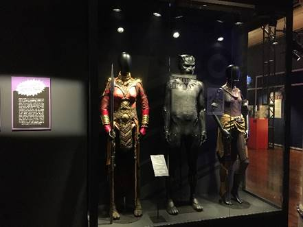 Three mannequins in costumes in case with text panel to left
