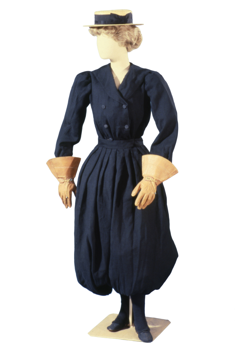 Mannequin wearing blue outfit with puffy bloomers, jacket with four button placket, large gloves, and a straw hat