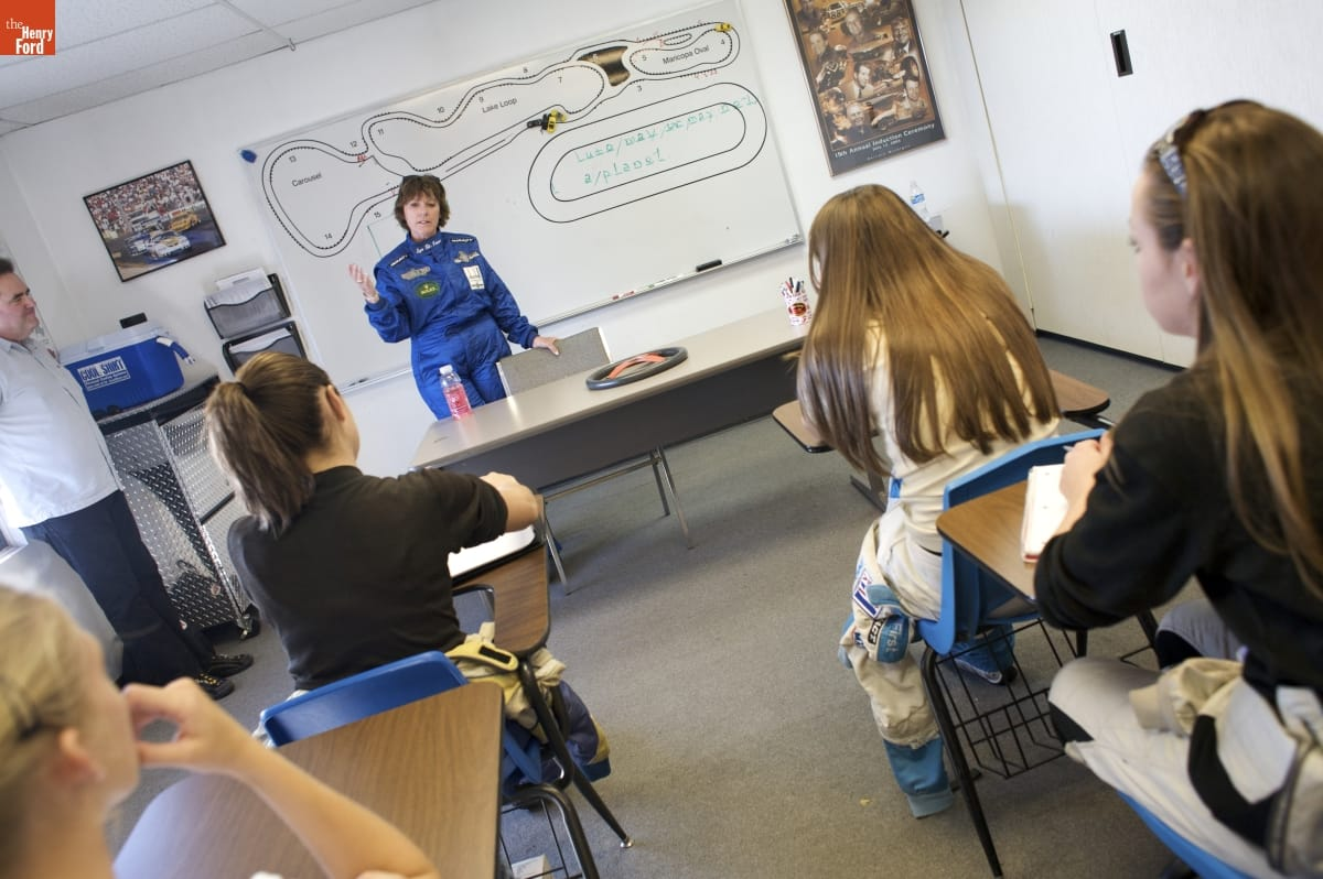 Woman in blue jumpsuit stands behind a table, in front of a whiteboard, at the front of a room with young women sitting in school desks