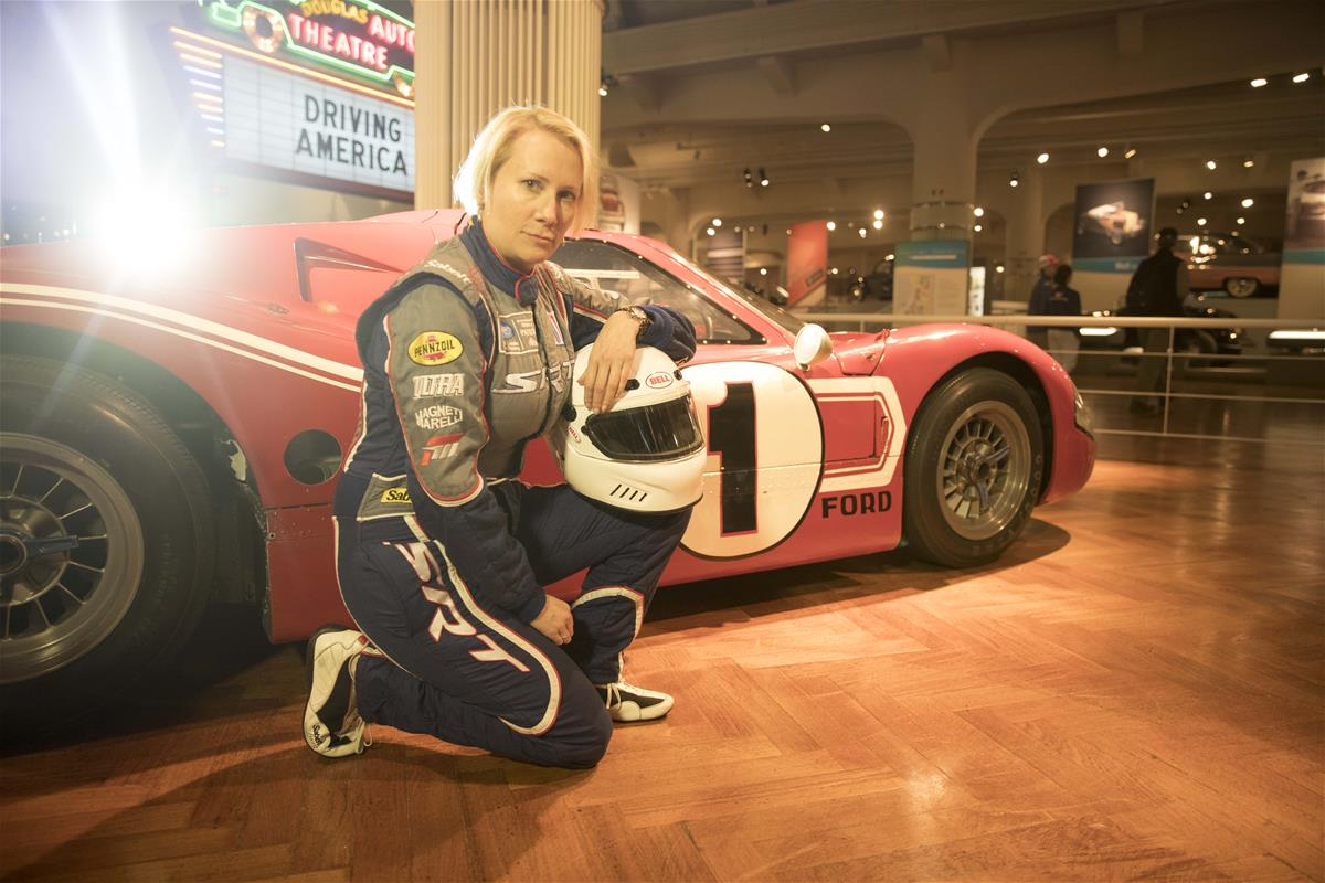 Woman in jumpsuit holding a helmet kneels on wood floor in a building next to low red race car with dramatic backlighting