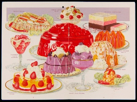 Colorful display of desserts on plates and platters and in decorative glasses; large red molded dessert in middle