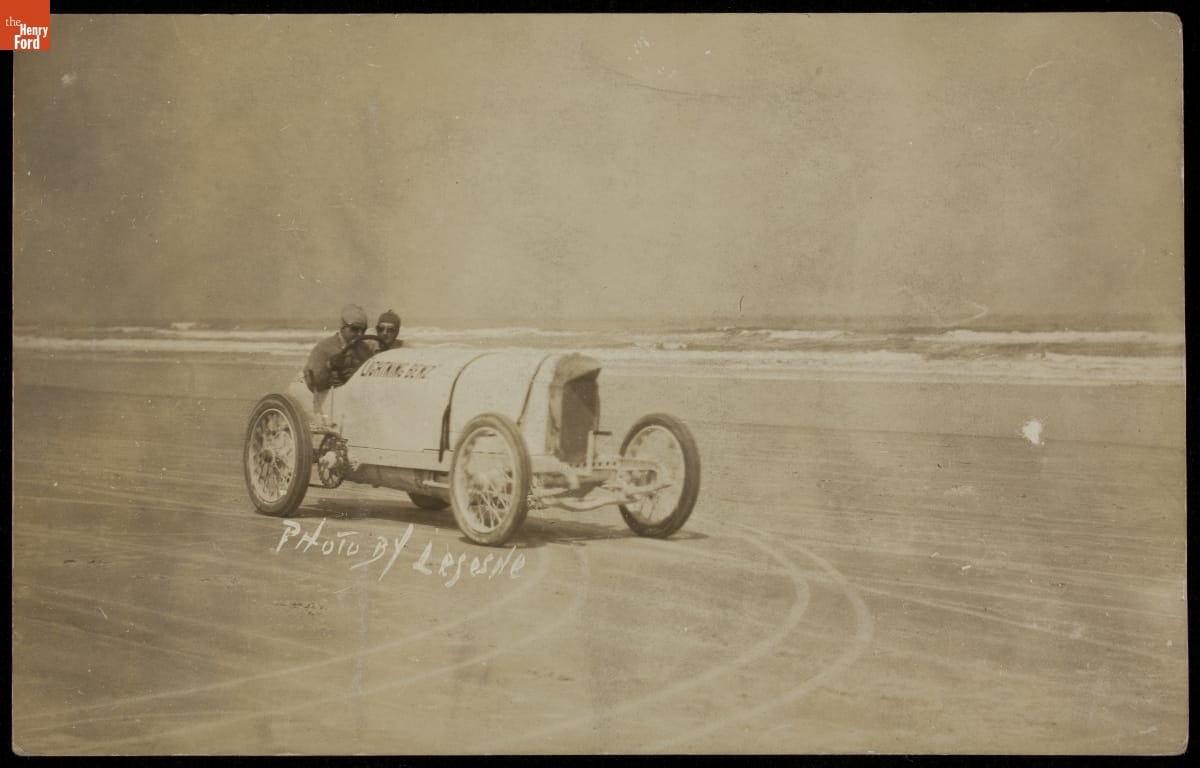 Sepia-tone photo of two men in early open race car on beach with ocean behind them; also contains text