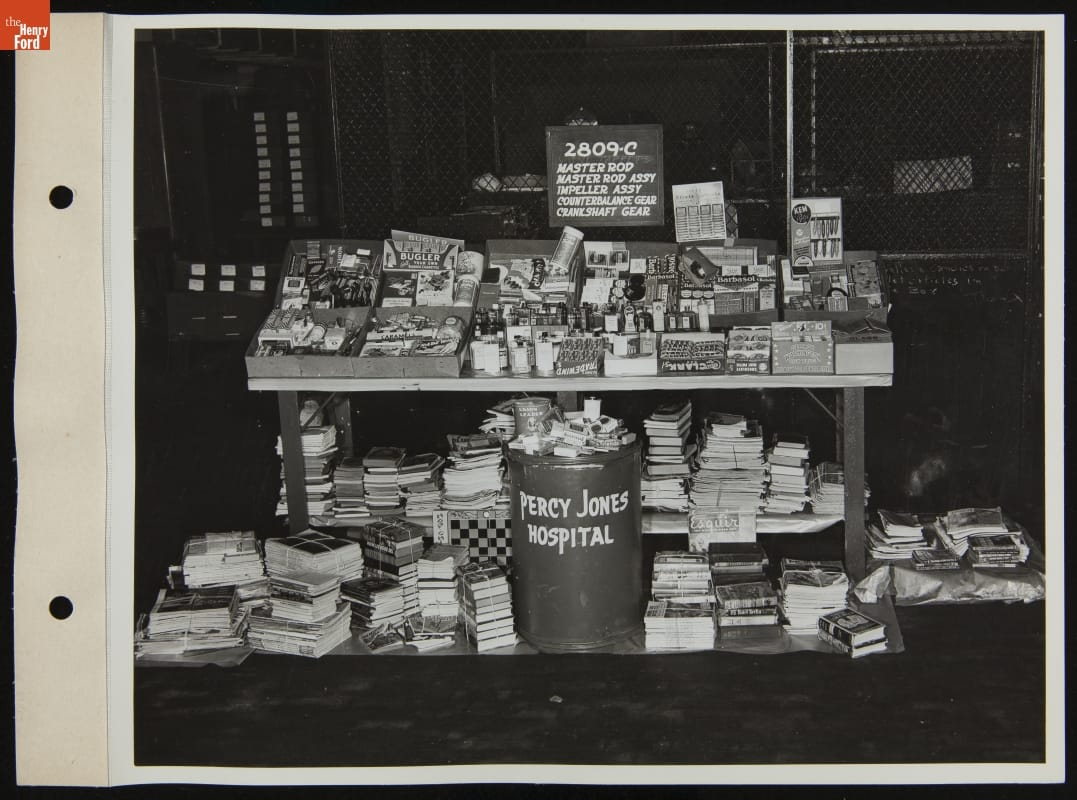 "Table piled with small items, books and magazines underneath, along with bin labeled ""Percy Jones Hospital"""