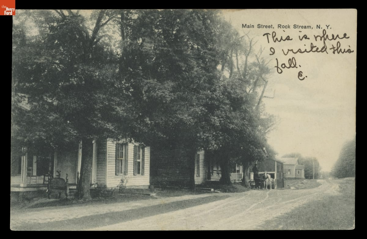 Black-and-white image of houses and trees along dirt road; printed and handwritten text
