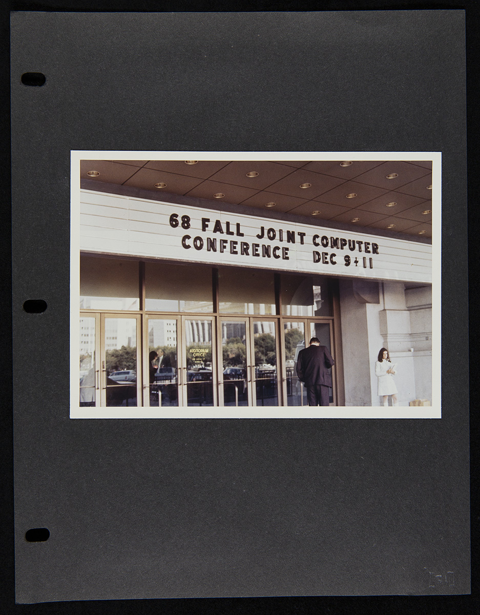 Three-ring binder black-colored page with a photo of entrance doors and a marquee with text; two people in front of doors