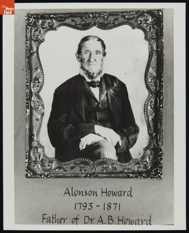 Portrait of man in suitcoat, jacket or vest, and tie, sitting with hands crossed on knee, in intricate frame; also contains text