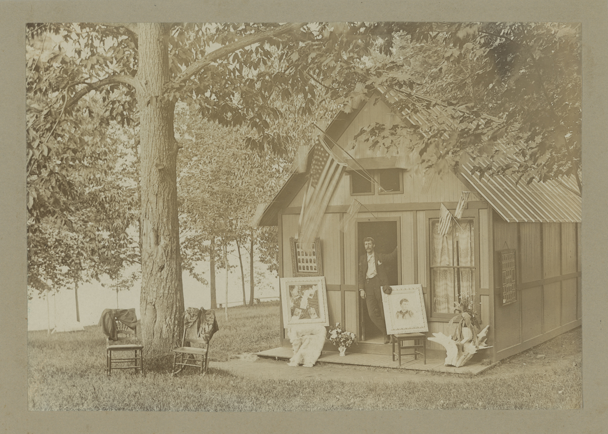 Man leaning in doorway of small wooden building in wooded location; chairs and portraits outside