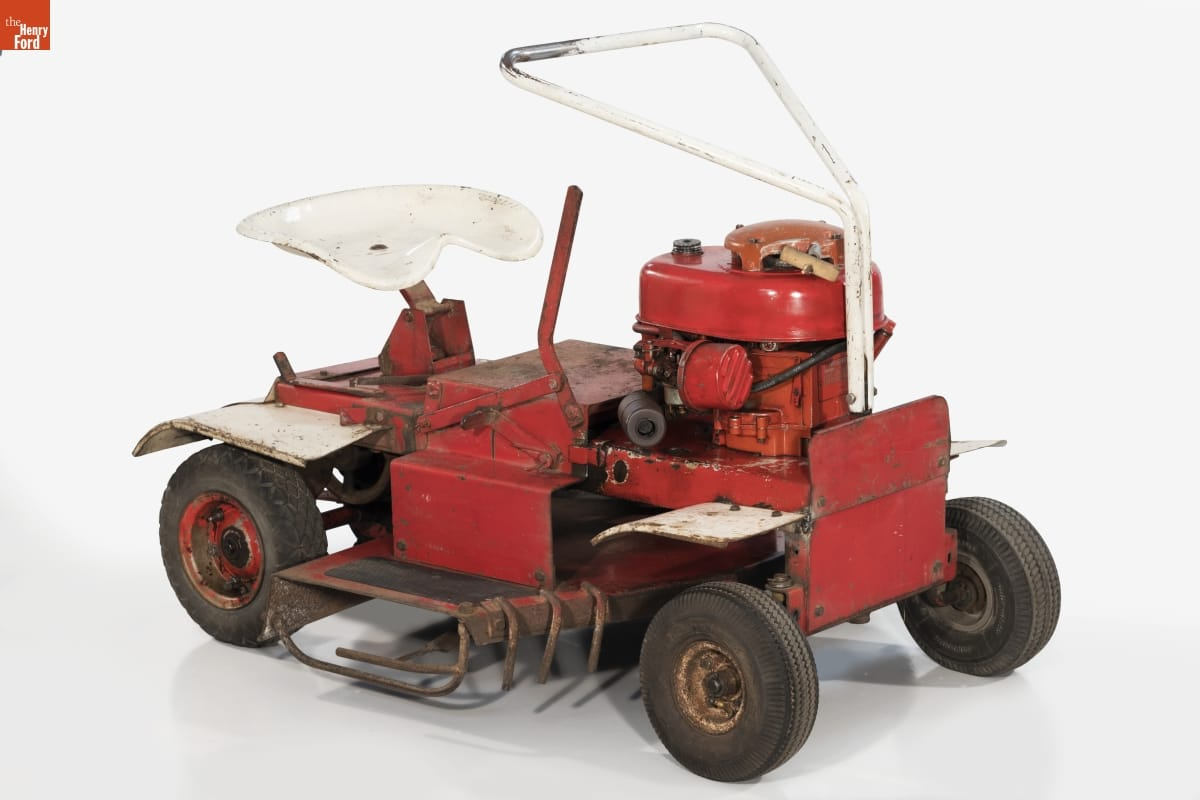 Simple red riding lawnmower with white metal seat and triangular handle