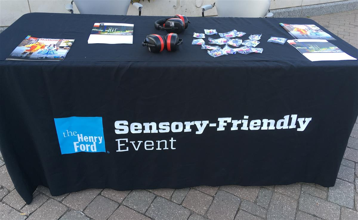 "Table covered in black cloth with text ""Sensory-Friendly Event"" and brochures and headphones on top"