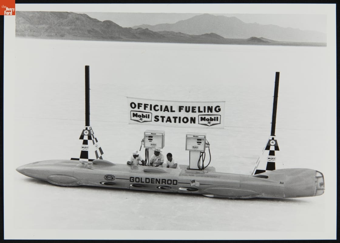 "Long, low, race car at gas pumps under banner reading ""Official Fueling Station,"" in open area with mountains in the background"
