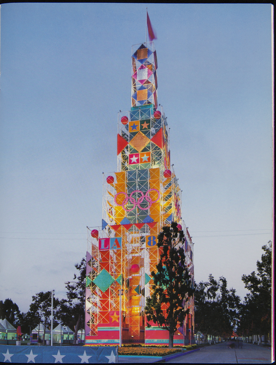 Large colorful tower with decorative scaffolding and images of stars, geometric shapes, and Olympic rings
