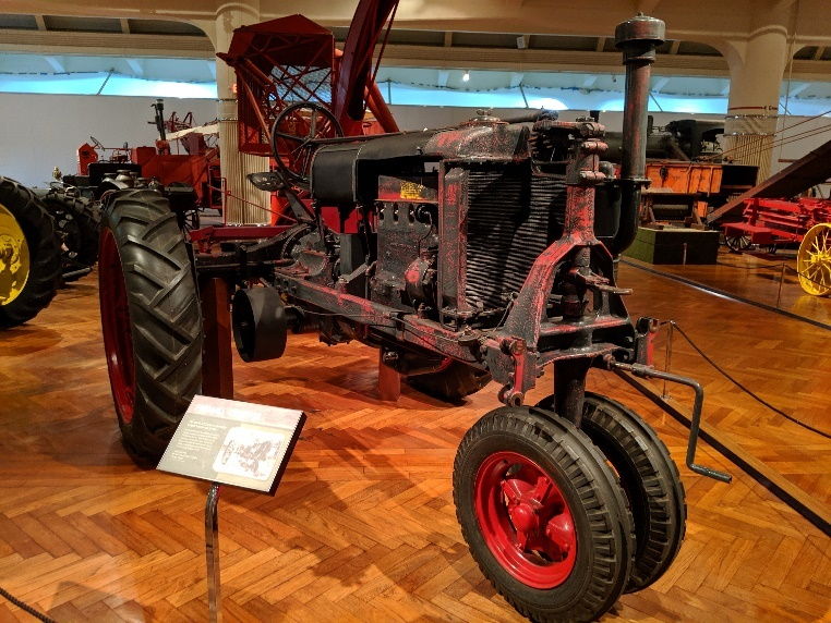 Tractor on wood floor in exhibit, surrounded by other equipment