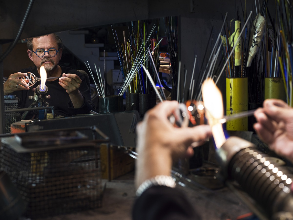 Man in workshop holds glass in a flame, seen in a reflection in a mirror on the wall
