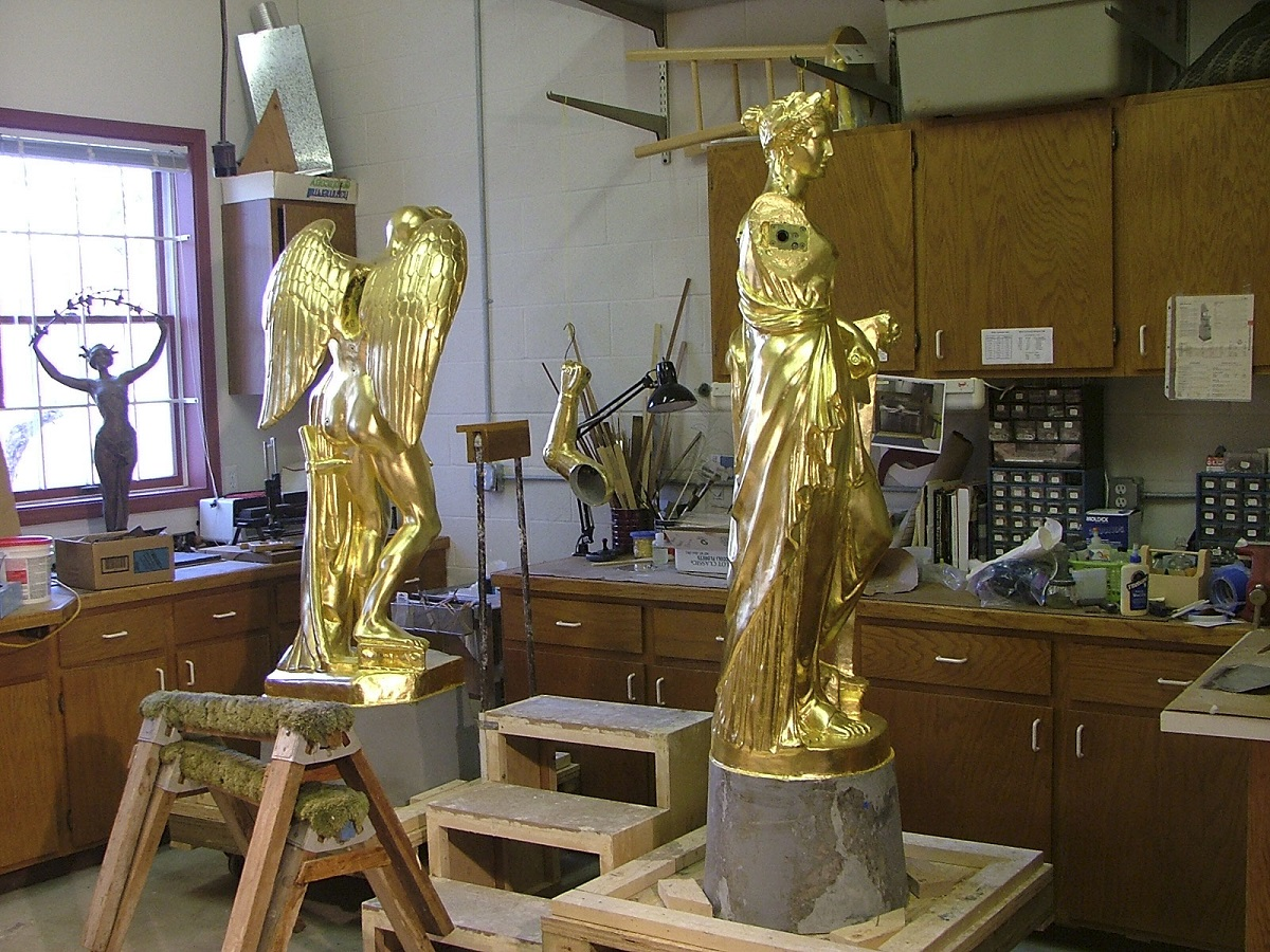 Two golden statues, one of a woman wearing flowing robes and one of a figure with wings, in a workroom