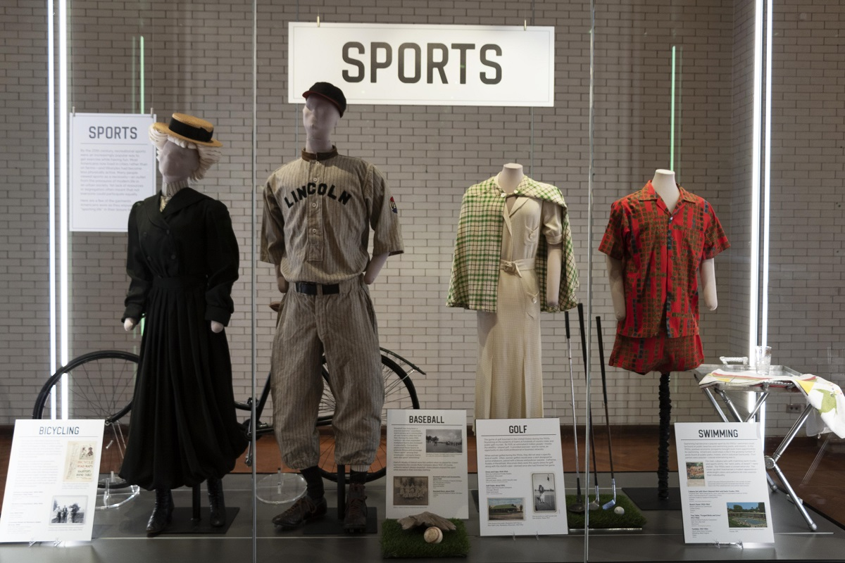 "Large glass case with large label ""Sports,"" other smaller labels, and four mannequins wearing various clothing"