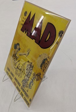Yellow MAD comic book covered in plastic and on stand