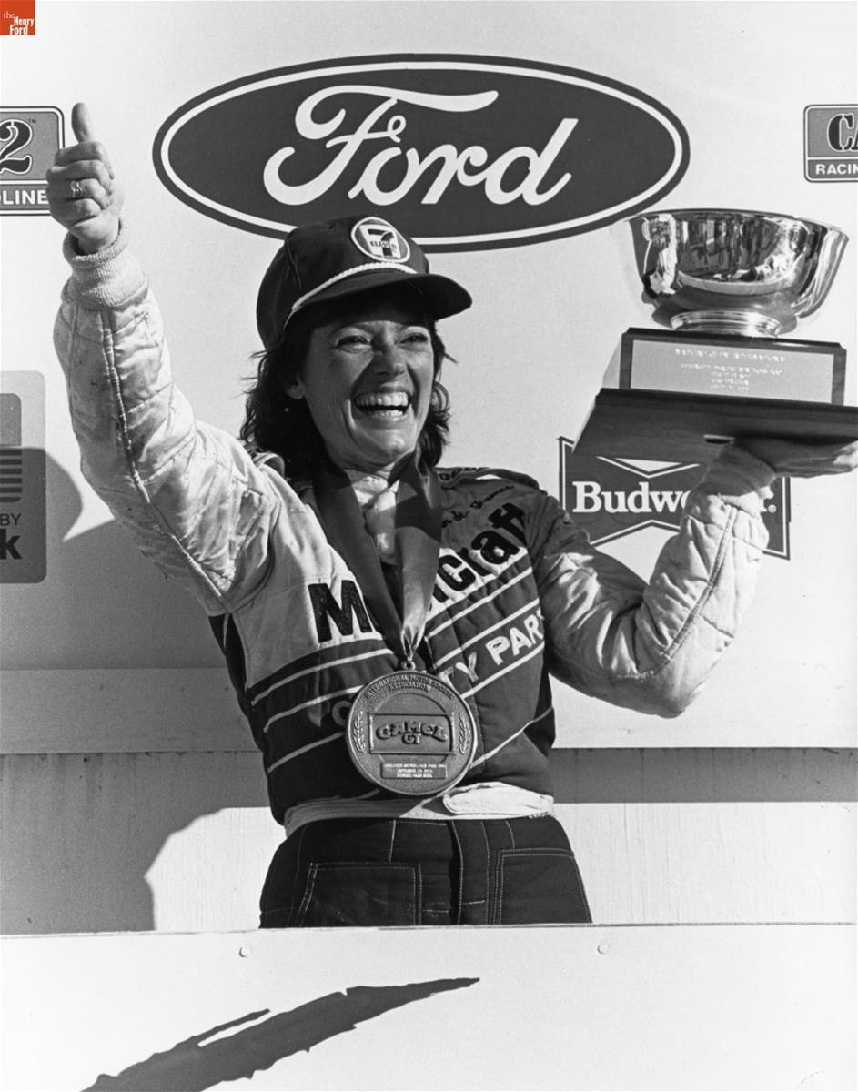 Smiling woman in a jumpsuit and baseball cap, with large medal around her neck, holds a trophy in one hand and makes a thumbs-up with the other, in front of a wall with Ford and Budweiser logos, among others