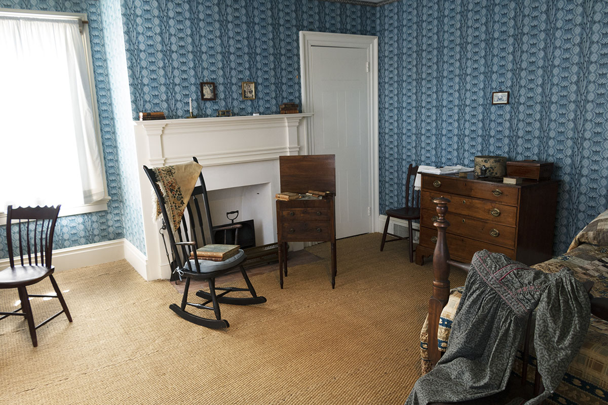 Room with patterned blue wallpaper containing fireplace, bed, chest of drawers, chairs