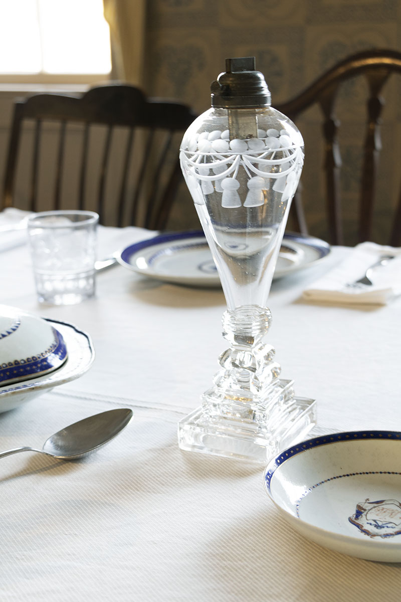 Clear glass lamp with etched pattern on tablecloth with dishes and silverware at place settings nearby