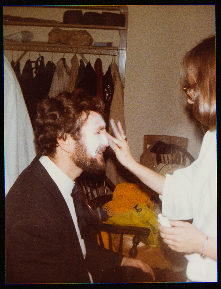 Seated man having makeup applied by a standing woman