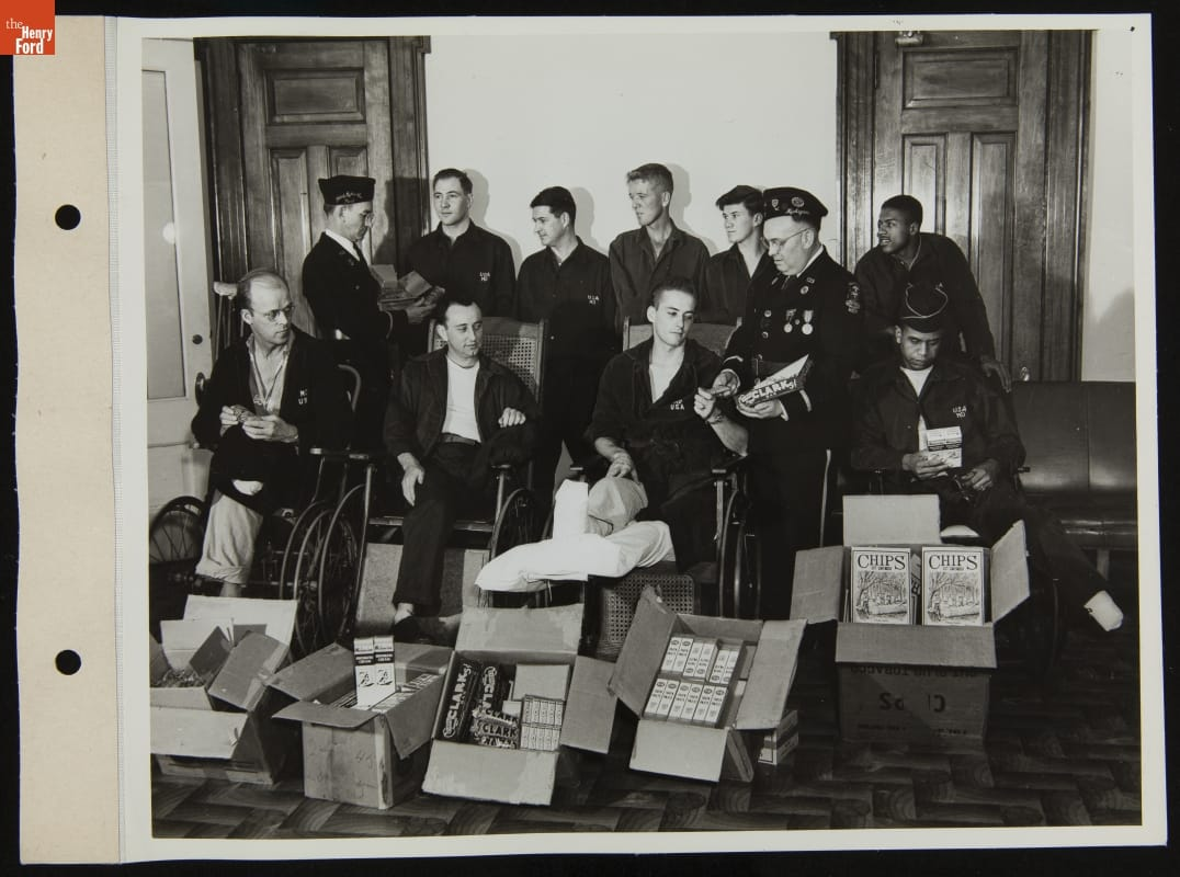 Group of men in robes and pajamas, some in wheelchairs, are handed items by two soldiers; additional items in boxes in front of the group