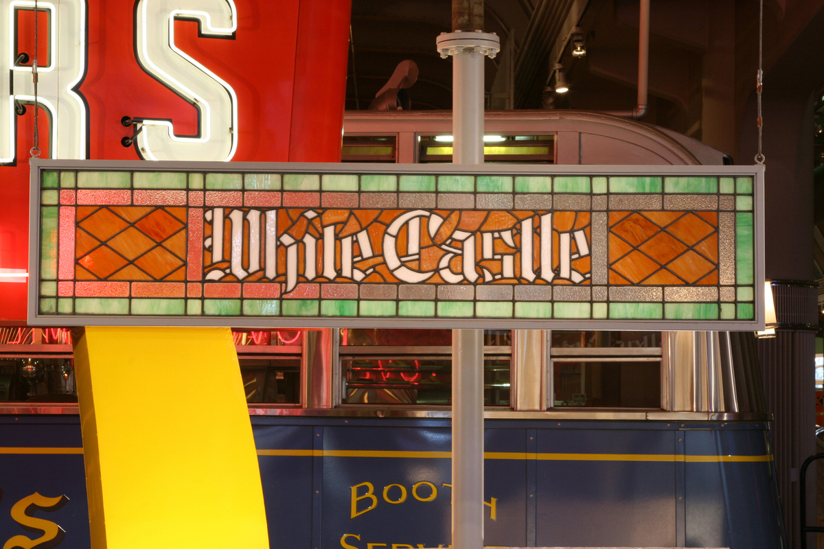 "Stained glass sign in red, orange, and green, with white text ""White Castle,"" with other items visible in background"