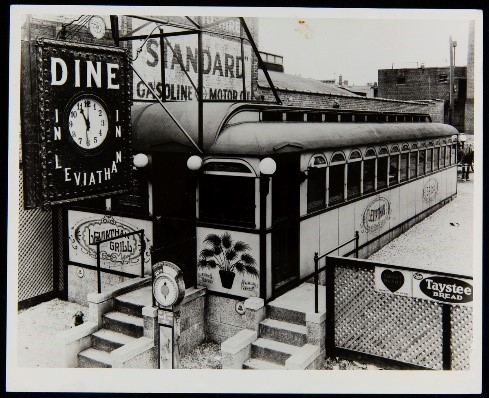 "Long low building with windows all along the side; clock hanging in front with text ""Dine in Leviathan"""