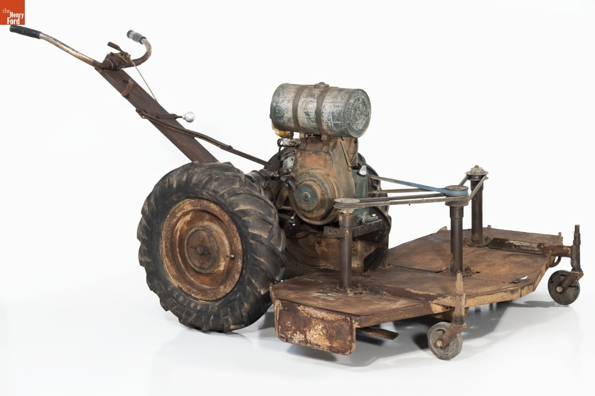Rough lawnmower with flat attachment and two small wheels in front; two large wheels behind; and crude handlebars