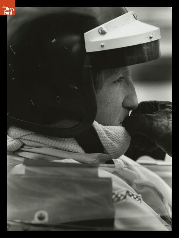 Close-up side view of man's head in crash helmet with a gloved hand to his mouth