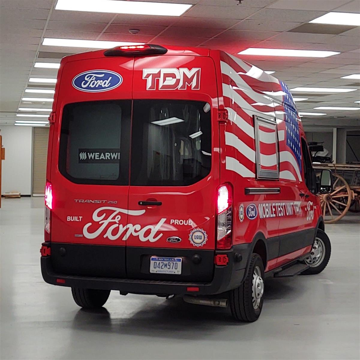 Rear view of red van with large back window; various text on vehicle and large American flag on visible side